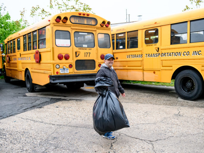 Man wearing a hat carrying a bag of trash in front of yellow school buses.