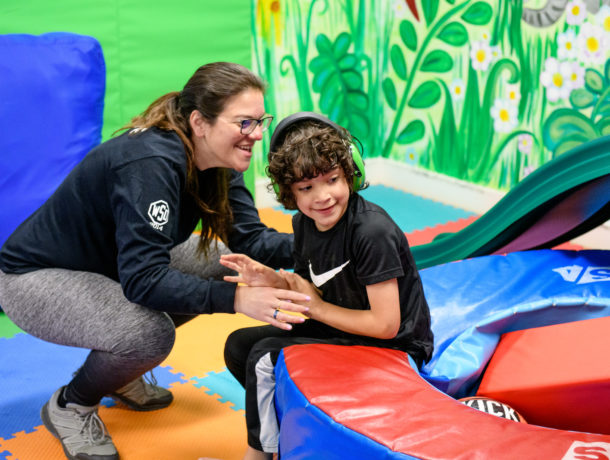 Woman is smiling as she supports a boy wearing headphones as he enjoys the colorful sensory gym
