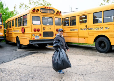 Man carrying trash bag in front of yellow school buses