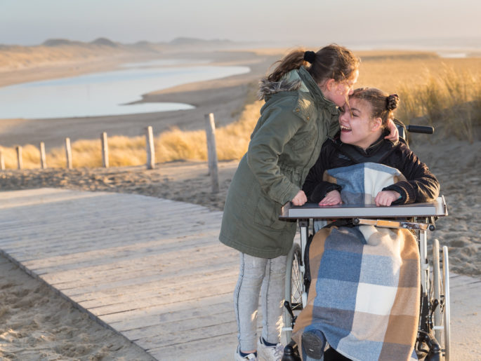 Woman in green jacket kisses another woman in a wheelchair on the forehead as they enjoy the seaside at sunset