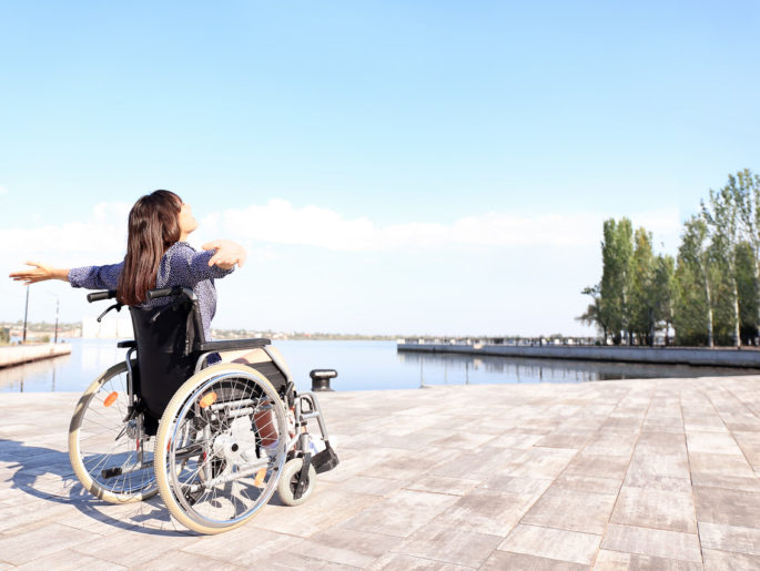 A woman with brown hair in a wheel chair spreads her arms out to enjoy the breeze over the water