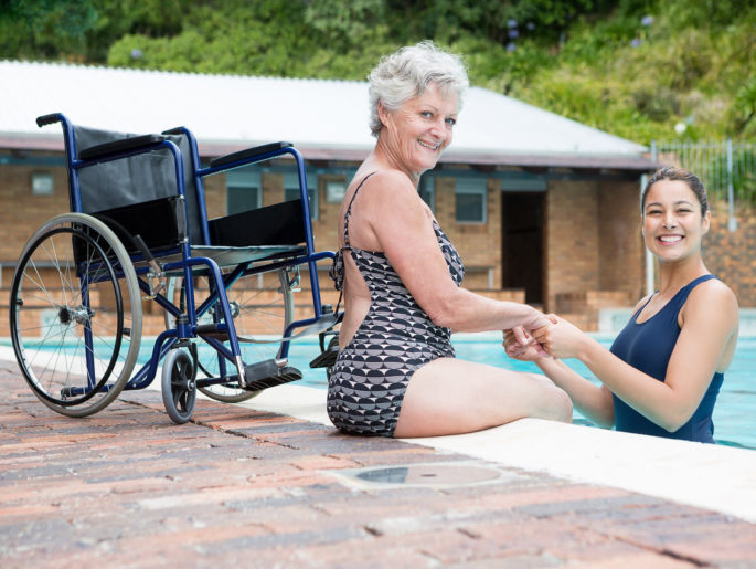 Woman with white hair in a bathing suit is sitting on the edge of the pool while she holds hands with a woman in a bathing suit standing in waist-deep water in the pool. Her wheelchair is seen adjacent to the scene.