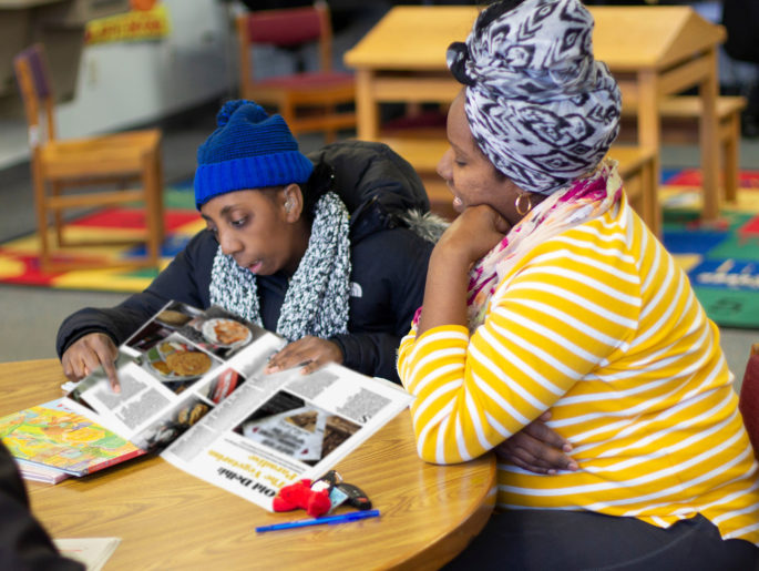 Two women sitting in the library reading
